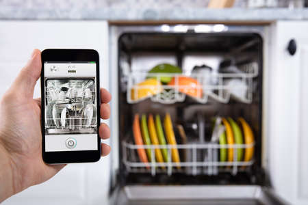 Close-up Of A Person's Hand Operating Dishwasher With Smartphone