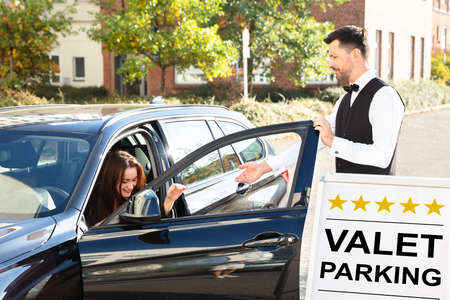 Happy Male Valet Opening Car Door Near Valet Parking Sign