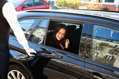 Close-up Of Man's Hand Opening Car Door While Smiling Young Woman Sitting In Car
