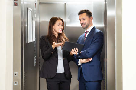 Smiling Young Businesswoman And Businessman Discussing While Using Digital Tablet Standing Near Elevator Banco de Imagens