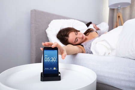 Young Woman Sleeping Near Alarm Set On Mobile Phone In Bedroom