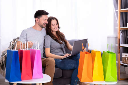 Smiling Young Couple Shopping On Laptop Near Colorful Shopping Bags