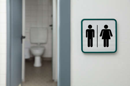 Public Restroom With Male And Female Toilet Sign On White Wall