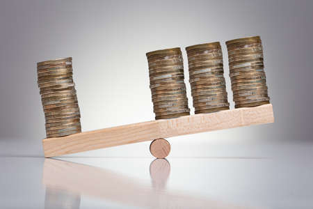 Stack Of Coins On Wooden Seesaw Over Gray Background Stock fotó