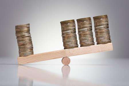 Stapel Münzen auf hölzerner Wippe über grauem Hintergrund