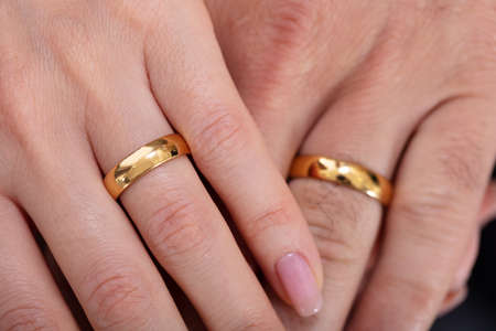 High Angle View Of A Couple's Hand Showing Their Wedding Rings