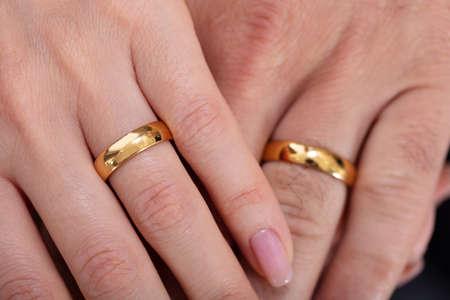 Veduta dall'alto della mano di una coppia che mostra le loro fedi nuziali