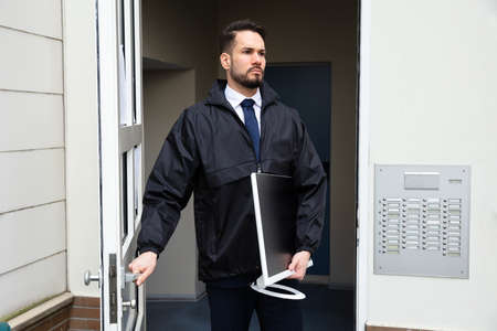 Young Male Technician Opening Door While Carrying Desktop In Hand Stockfoto
