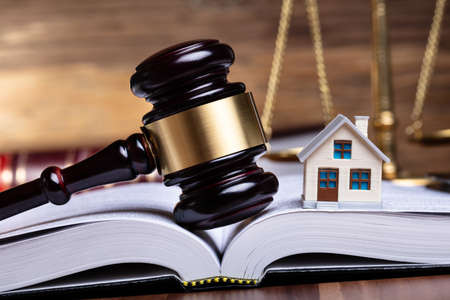Close-up Of Miniature House And Gavel On Open Book Imagens