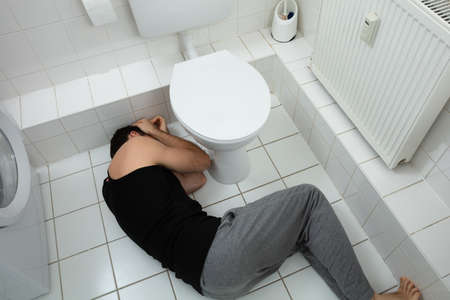High Angle View Of Alcoholic Man Sleeping Near Toilet Bowl In Restroom