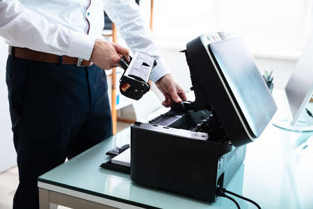 Mid-section Of Businessman Fixing Cartridge In Printer At Workplace