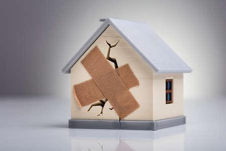 Gebroken huismodel met gekruiste pleister op bureau Stockfoto