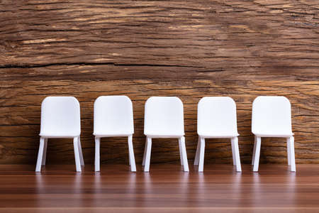 Miniature Chair In A Row On Wooden Background 免版税图像