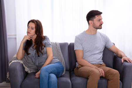 Upset Young Couple Sitting On Sofa At Home Imagens