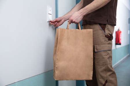 Delivery Man Ringing The Door Bell With A Brown Paper Bag In His Hand
