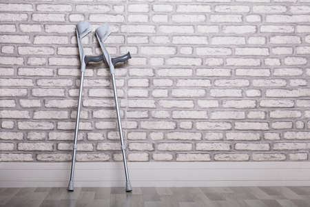Pair Of Crutches Leaning Against Brick Wall