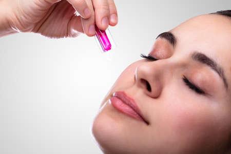 Close-up of Young Woman's Hand Squeezing Capsule de vitamine sur le visage