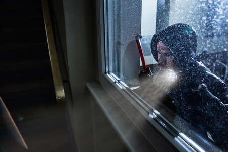 Cambrioleur avec pied de biche et lampe de poche à la recherche dans une maison Windows Banque d'images
