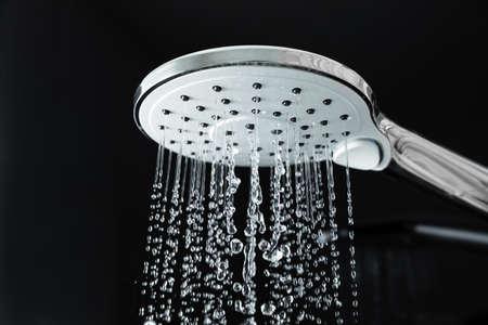 Close-up van water dat uit de douche in de badkamer stroomt