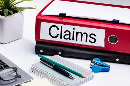 Carpeta de reclamaciones y suministros de oficina sobre escritorio blanco