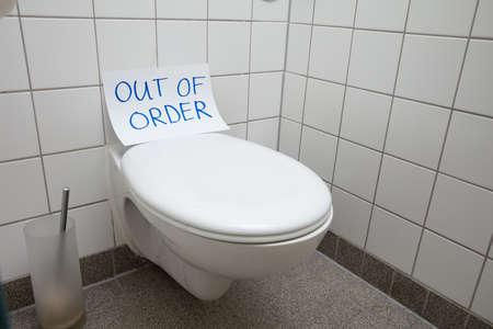 Geschriebener Text außer Betrieb Nachricht auf Papier über Toilettenschüssel im Badezimmer
