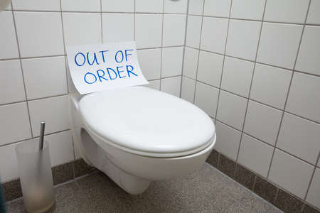 Written Text Out Of Order Message On Paper Over Toilet Bowl In Bathroom