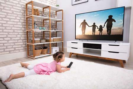 Rear View Of Innocent Girl Lying On Carpet Watching Television