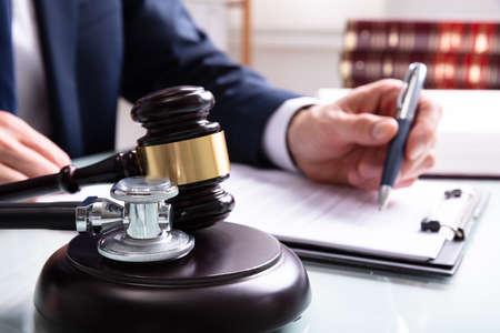 Giudice che scrive su documenti legali con un martello e uno stetoscopio sul blocco del suono in tribunale