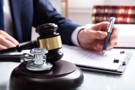 Sędzia piszący dokumenty prawne za pomocą młotka i stetoskopu nad blokiem dźwiękowym w sądzie