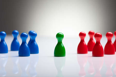 Close-up Of Colorful Pawns On The Reflective Desk Against Gray Background