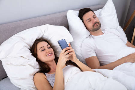 Smiling Woman Using Smartphone While Her Husband Sleeping On Bed In Bedroom Standard-Bild
