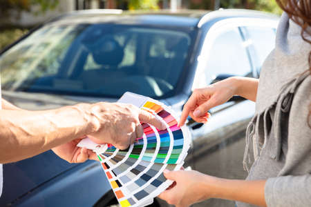 Close-up Of Man Showing Color Samples To Woman Standing In Front Of Car