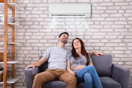 Feliz pareja joven sentada bajo el aire acondicionado en el sofá en casa