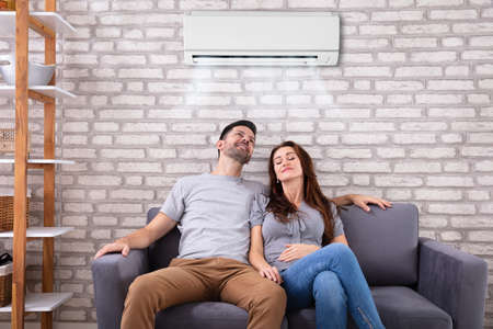 Szczęśliwa młoda para siedzi pod klimatyzatorem na kanapie w domu