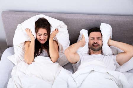 Couple perturbé couvrant leurs oreilles avec un oreiller sur le lit Banque d'images