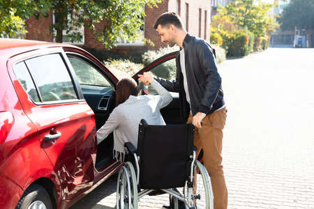 Close-up Of Man With Her Wife Sitting On Wheelchair Moving Towards Car Stock Photo