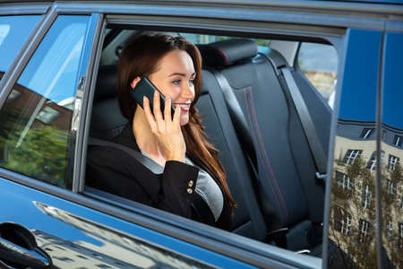 Happy Young Businesswoman Sitting Inside Car Talking On Smartphone