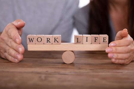 Close-up de la mano de la pareja protegiendo el trabajo y la vida, equilibrio de bloques de madera en balancín Foto de archivo