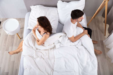High View Of Despaired Married Couple Back To Back On Bed