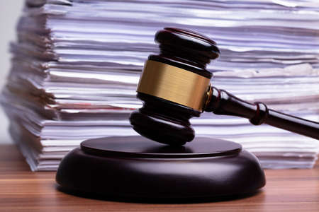 Wooden Judge Gavel In Front Of Stacked Files On Wooden Table