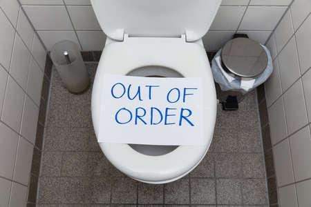 Geschriebener Text außer Betrieb Nachricht auf Papier über Toilettenschüssel im Badezimmer Standard-Bild