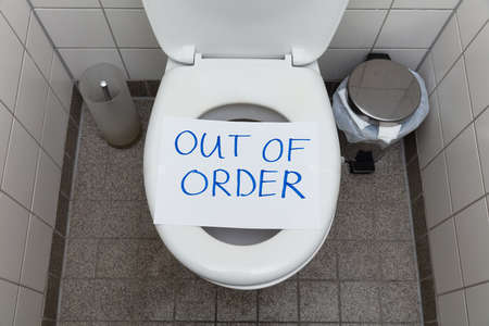 Mensaje de texto escrito fuera de servicio en papel sobre la taza del inodoro en el baño Foto de archivo
