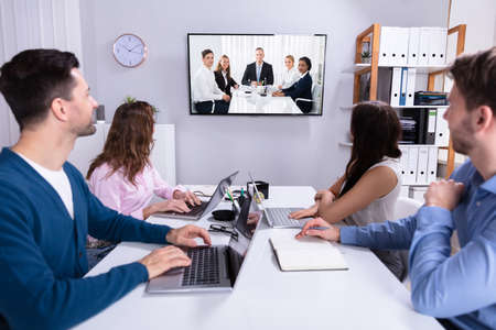 Rear View Of Businesspeople Attending Videoconference Meeting In Office