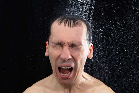 Portrait Of Young Man Taking Cold Shower In Bathroom Standard-Bild