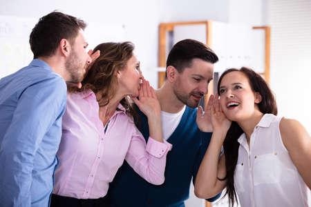 Colega de negocios susurrando un chisme secreto a una mujer sorprendida sorprendida con la boca bien abierta Foto de archivo
