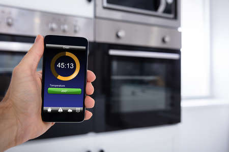 Close-up Of A Person Hands Operating Oven Application With Cellphone Stock Photo