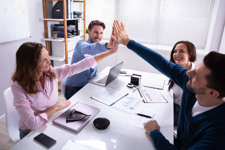 Group Of Happy Businesspeople Giving High Five Over Desk At Workplace Imagens