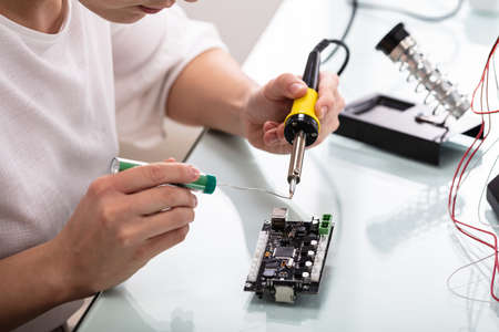 Female Engineer Or Tech Repairs Electronic Device In Hardware Repair Shop