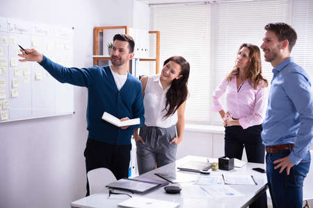 Young Male And Female Businesspeople Standing Near Scrum Task Board In Office Stock Photo