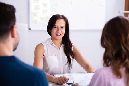 Businessman And Businesswoman Taking Interview Of Young Smiling Woman Stock Photo